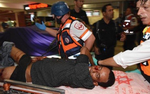 Mulu Habtom Zerhoma, a wounded Eritrean, is evacuated from the scene of an attack in Beersheba, Israel, on Oct. 18, 2015. [AP Photo/Dudu Grunshpan]