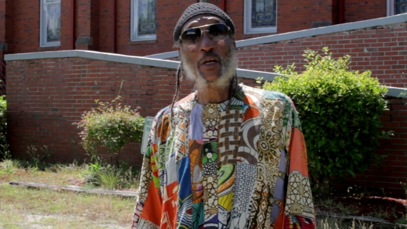 "Activist & Radio Host Larry Reni Thomas declares sadly ""Wilmington – the town – is synonymous with racial violence."" Thomas ceaselessly fights on behalf of descendants of the victims of the 1898 Wilmington riot."